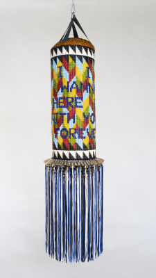 Jeffrey Gibson, I WANNA STAY HERE WITH YOU FOREVER, 2019, repurposed punching bag, repurposed wool army blanket, glass beads, metal studs, tin jingles, artificial sinew, nylon fringe, and steel, Dallas Museum of Art, TWO x TWO for AIDS and Art Fund, 2019.87. Courtesy of the artist and Roberts Projects, Los Angeles, California. © Jeffrey Gibson